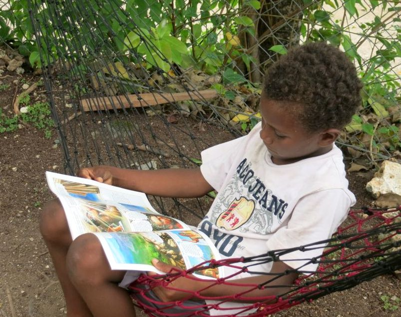 10-year-old Timmy enjoys reading a Bible Comic in his language, Arosi.