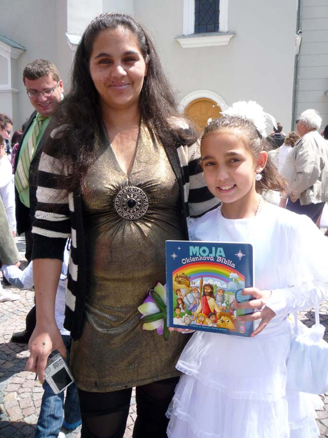 A proud Roma mother and her daughter, who received a Scripture book when she took her first communion