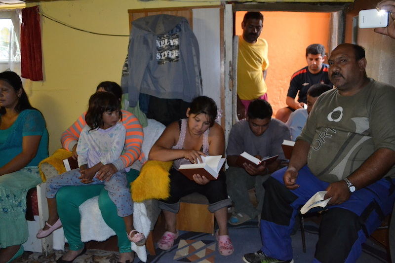 Members of a Romani house church in the village of Rozkovany read their new Bibles