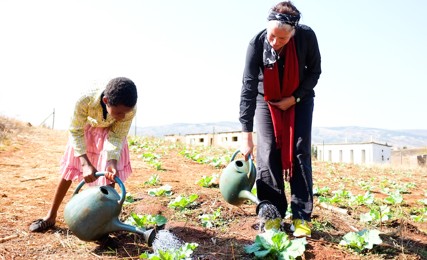 A young orphan girl waters vegetables with Synne Garff, a visitor from the Danish Bible Society. The children are taught how to grow their own vegetables. (Photo © Adam Garff/Danish Bible Society)