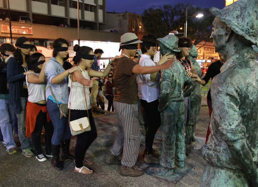 Students explore the city blindfolded, led by a blind guide.