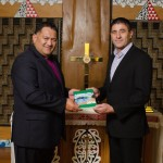 Anglican Bishop Kito Pikaahu receives the new Gospel of Luke (Te Rongopai a Ruka) from Steve McRobie of the Bible Society.