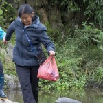 Simei Tong leading her blind friend, Zhou Maoying, across the stream by Luo Shui church.
