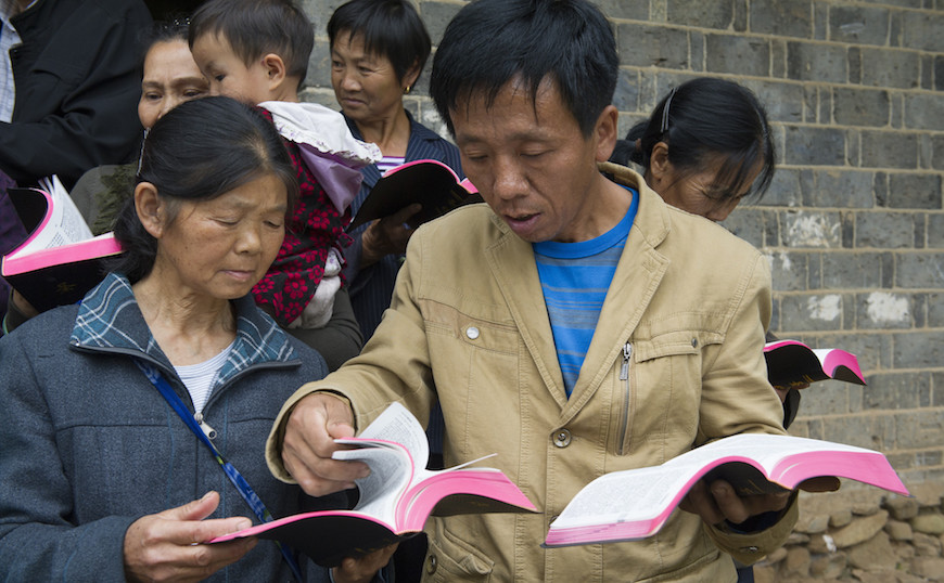 Tong Xin Jun, the church's leader, helps Simei Tong find the right page in her new Bible.
