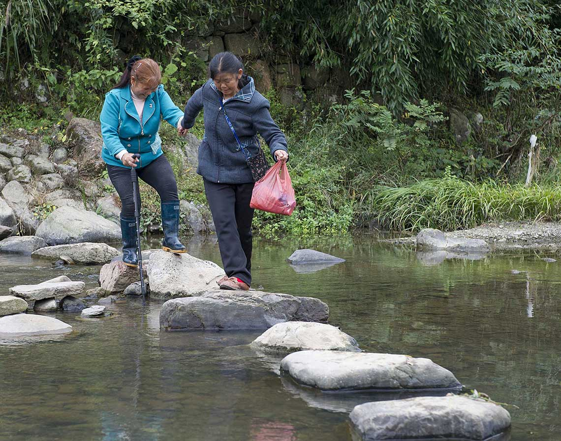 Simei Tong leading her blind friend, Zhou Maoying, across the stream by their church.