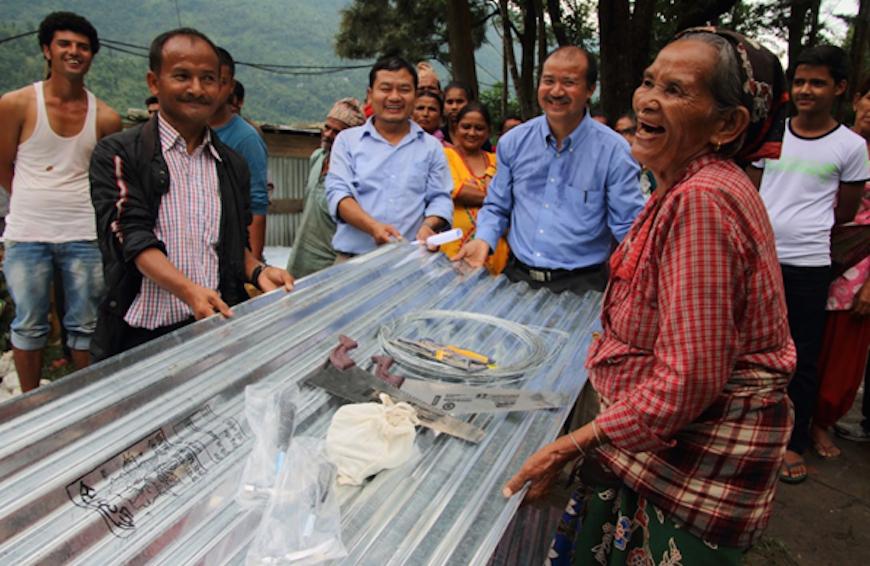 Una pobladora de Lamosanghu, una localidad que fue fuertemente afectada por el terremoto, se ríe con Tej Jirel y personal de la Sociedad Bíblica y voluntarios al recibir láminas para techo y herramientas que necesita para construir un refugio para ella.