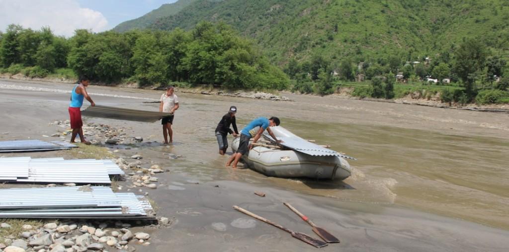 Uso de una lancha de hule para transportar las láminas de techo y cruzar el río Sunkoshi, Distrito de Ramechhap