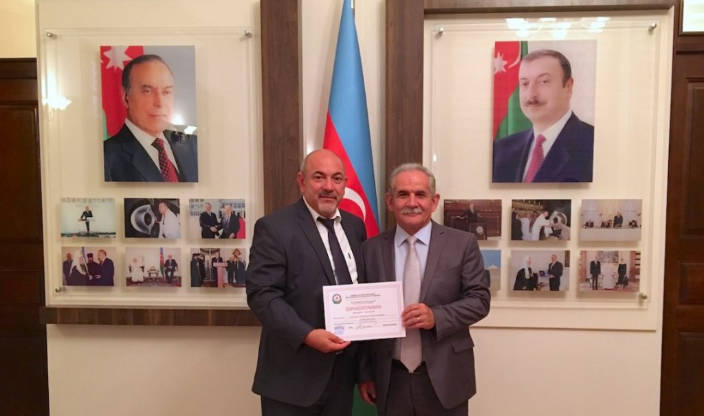 Rasim Khalilov (left), Chairman of the Bible Committee, which has been working for more than a year to get the Bible Society in Azerbaijan officially registered, holds the new certificate of registration.