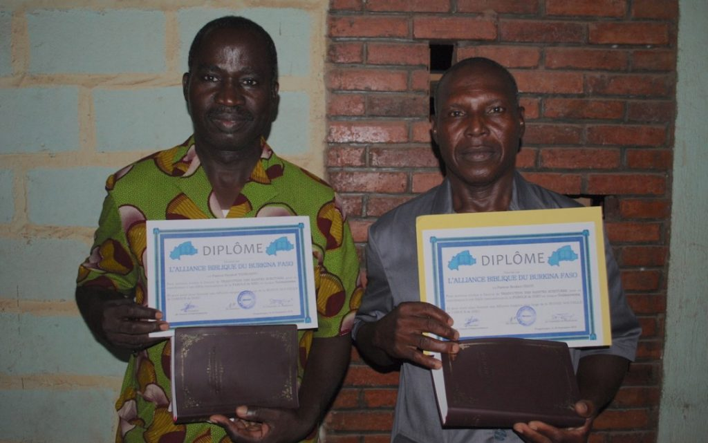 Gulmancema Bible translators Pastor Abraham Tankoano (left) and M. Naba Grégoire with the certificates they were presented with at the dedication ceremony.