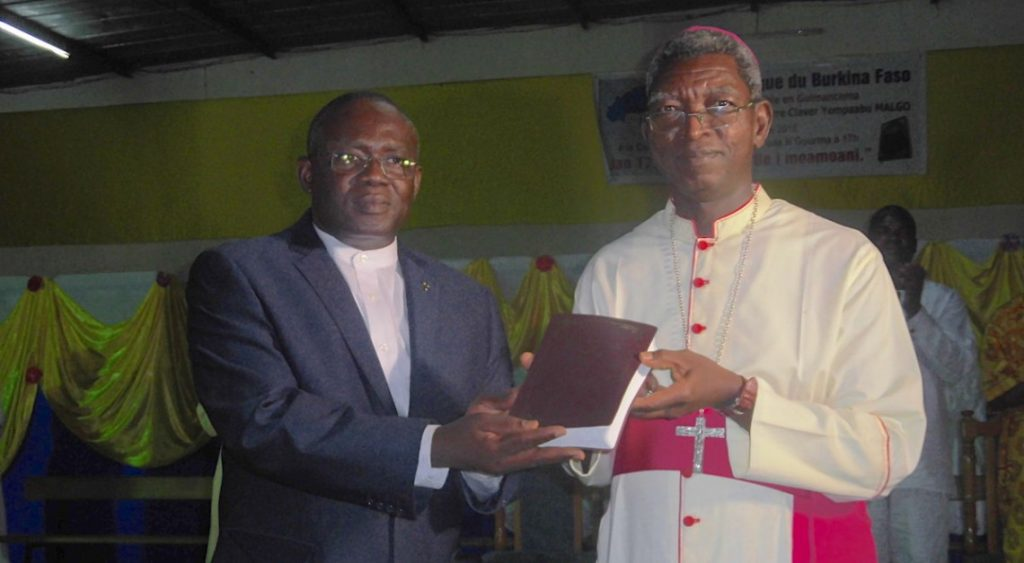 Mgr Pierre Claver Malgo (right) receives the Gulmancema Bible from Pastor Dramane Yankiné, General Secretary of the Bible Society of Burkina Faso.