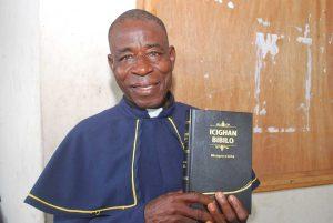 Rev Gideon Gandekaka holding the Tiv Bible